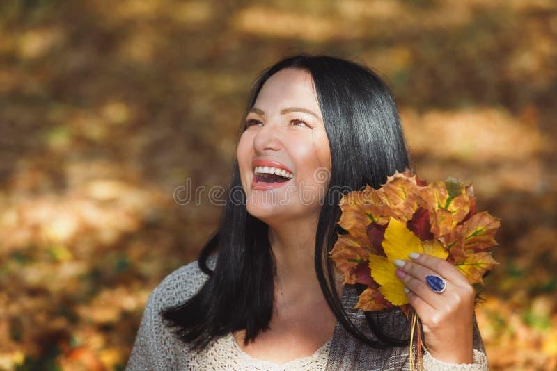 Kvinna som tycker om höstdag i parkera royaltyfri bild