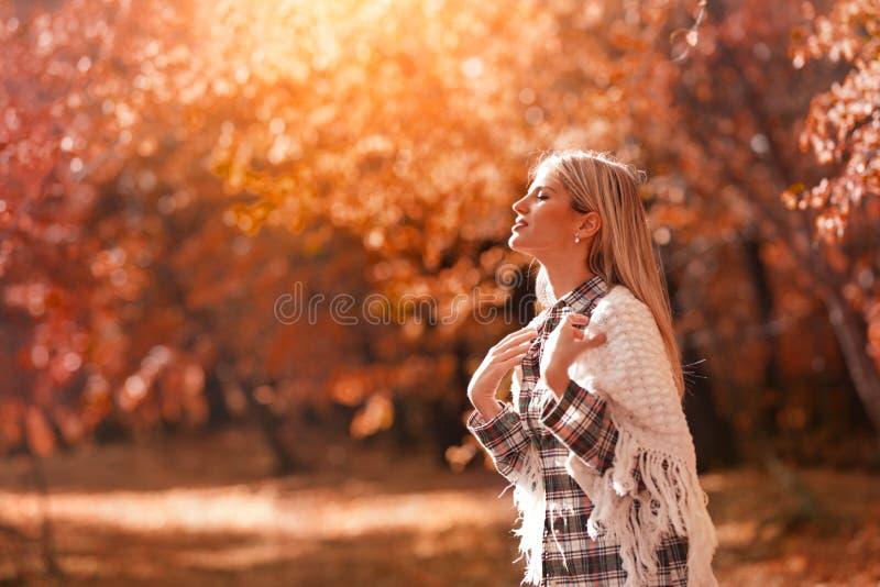 Kvinna som tycker om höstsolen som värme royaltyfria foton