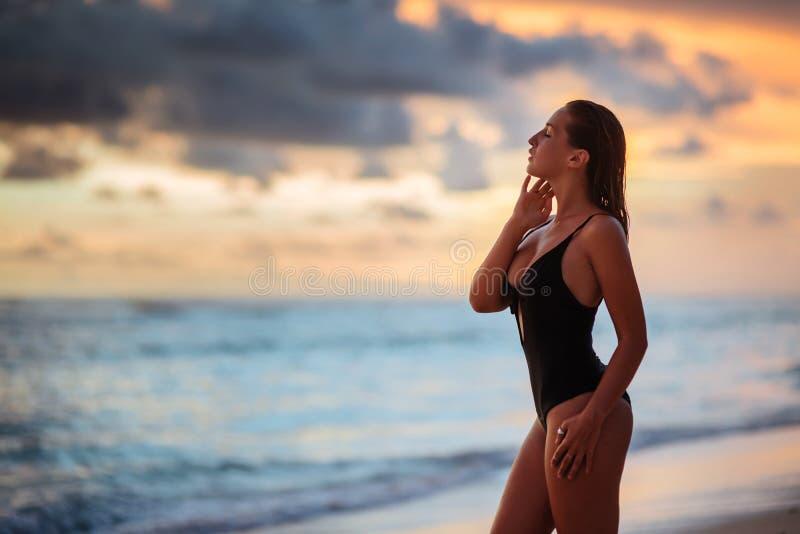 Kvinna som tycker om h?rlig solnedg?ng p? stranden royaltyfri bild