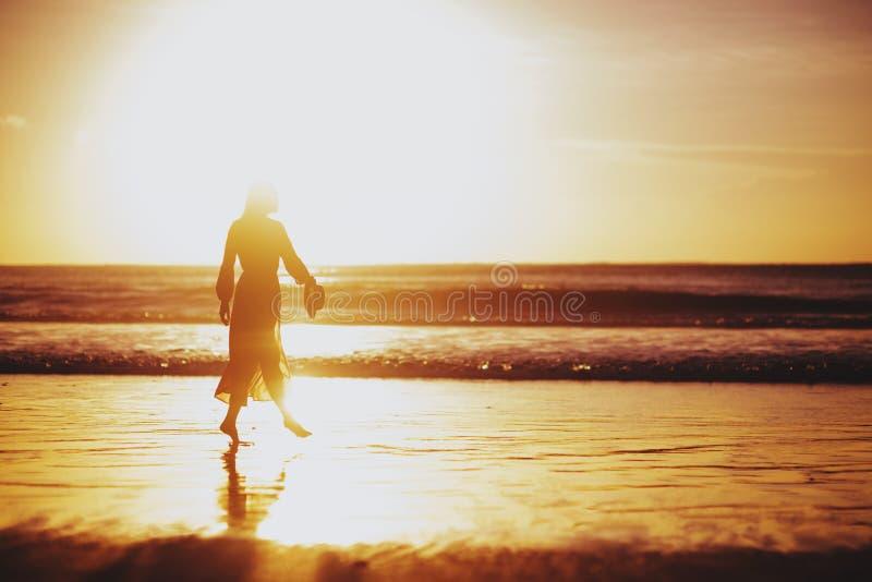 Kvinna som tycker om h?rlig solnedg?ng p? stranden arkivfoton