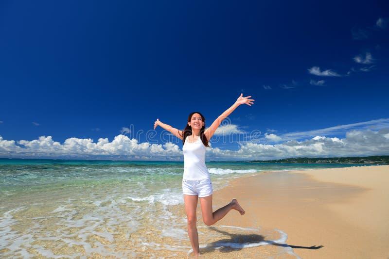 Kvinna som tycker om havet i Okinawa royaltyfria bilder