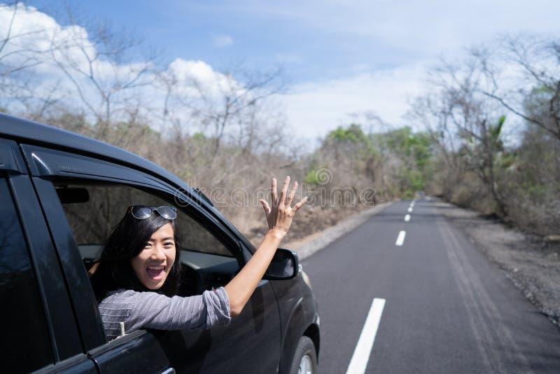 Kvinna som tycker om hennes tur som går på semester med bilen arkivfoto