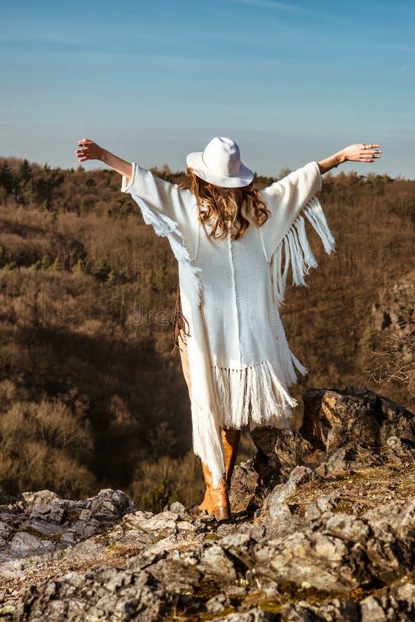 Kvinna som tycker om känslan av frihet som går i bergen arkivfoton