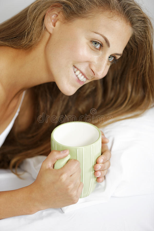 Kvinna som tycker om kaffe i säng royaltyfri fotografi