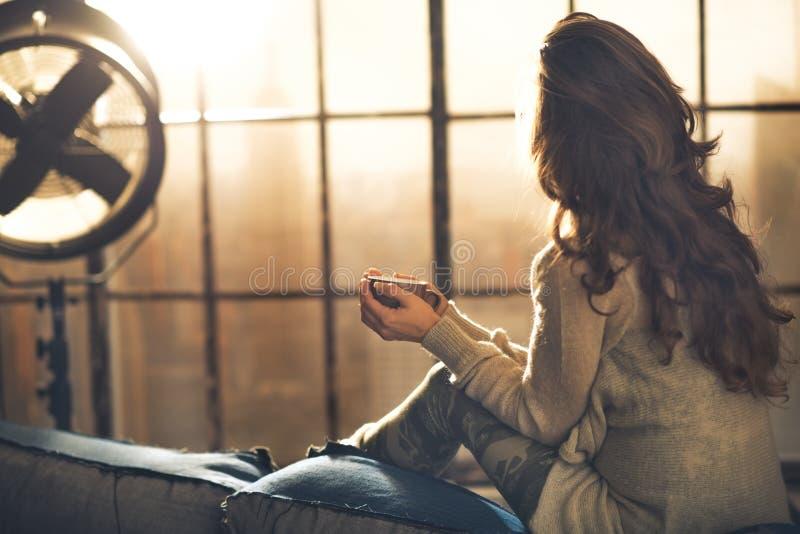 Kvinna som tycker om koppen av drycken i vindlägenhet royaltyfri foto