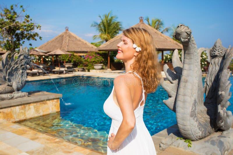 Kvinna som tycker om semester i tropisk lyxig semesterort arkivfoto