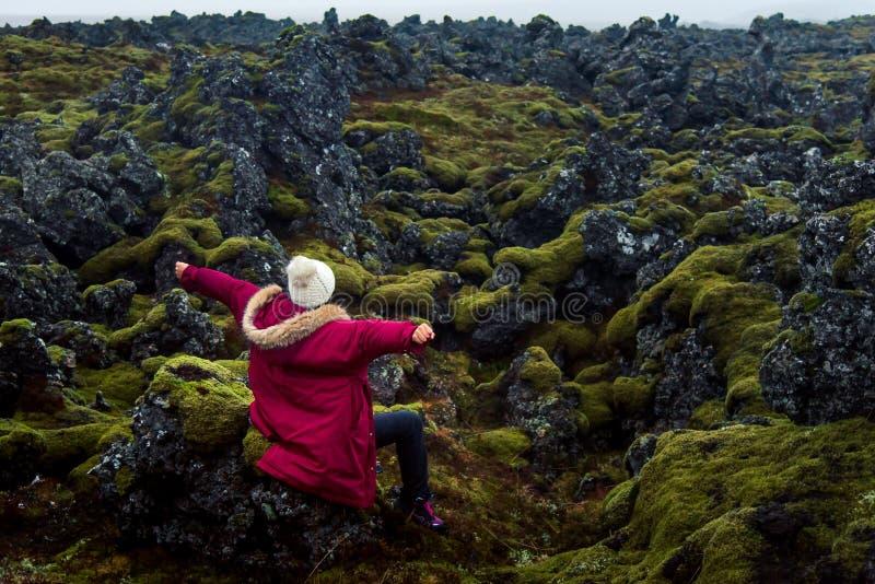 Kvinna som tycker om sikt för lavafält i Island royaltyfri foto