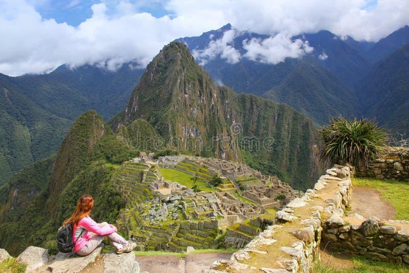 Kvinna som tycker om sikten av den Machu Picchu citadellen i Peru arkivfoton