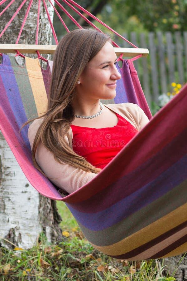 Kvinna som tycker om sommar i hängmatta royaltyfria bilder