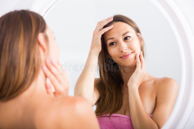 Kvinna som undersöker hennes framsida, genom att se den i spegel royaltyfri bild