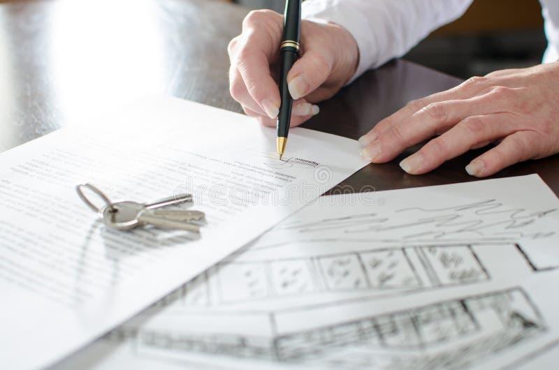 Kvinna som undertecknar ett fastighetavtal arkivbilder
