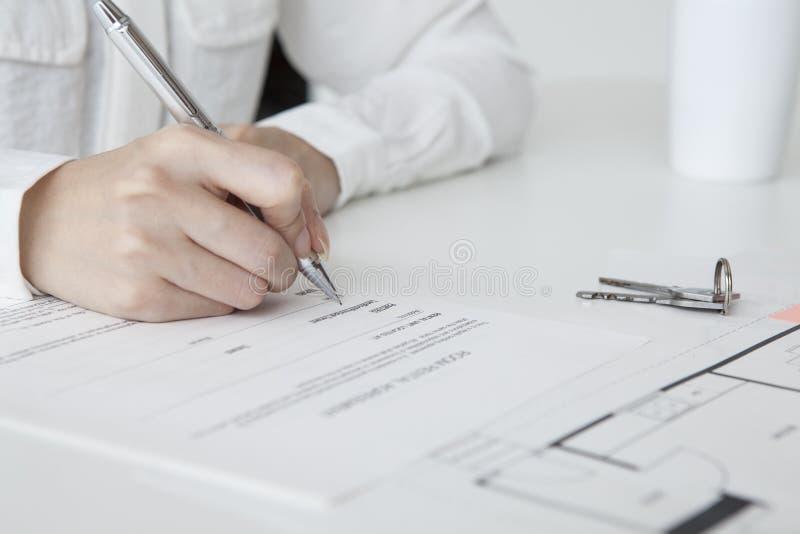 Kvinna som undertecknar ett fastighetavtal royaltyfria foton