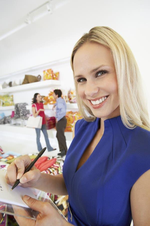 Kvinna som undertecknar ett kvitto i lager för hem- inredningar royaltyfria foton