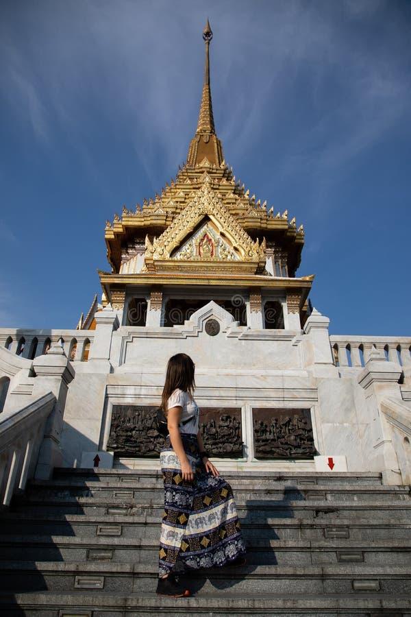 Kvinna som upp går trappan på den thai templet royaltyfri fotografi