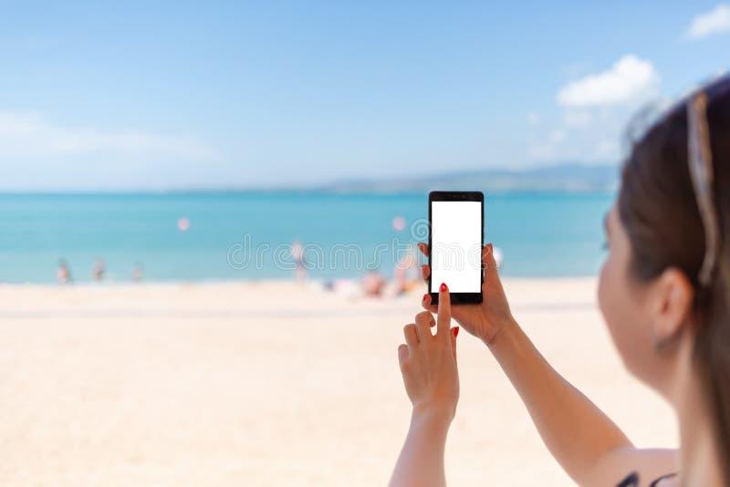 Kvinna som upp rymmer en smart telefon p? stranden Hav, sand och himmel p? bakgrunden Begrepp av den moderna teknologi och intern arkivfoton