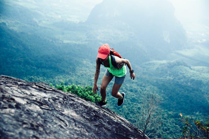 Kvinna som upp till kör bergöverkanten royaltyfria foton