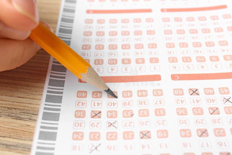 Kvinna som ut fyller lottsedeln med blyertspennan på trätabellen, closeup fotografering för bildbyråer