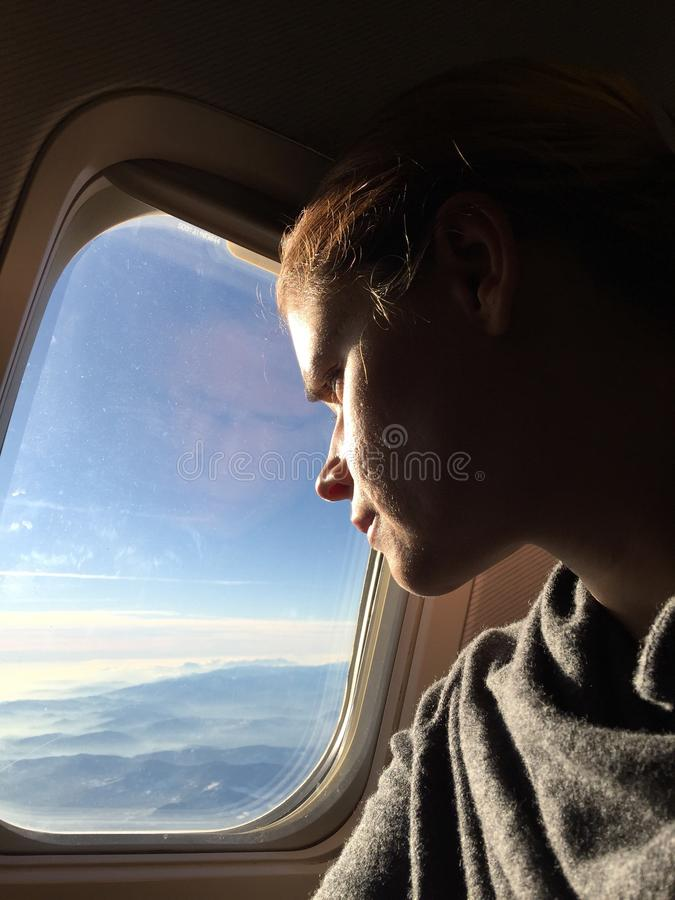 Kvinna som ut håller ögonen på fönstren av ett flygplan royaltyfria foton