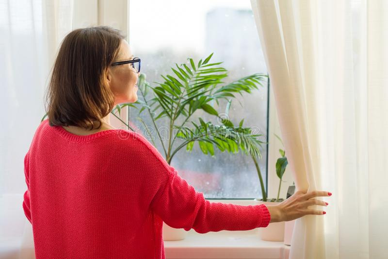 Kvinna som ut ser fönstret som öppnar gardinerna, sikt från baksidan royaltyfria bilder