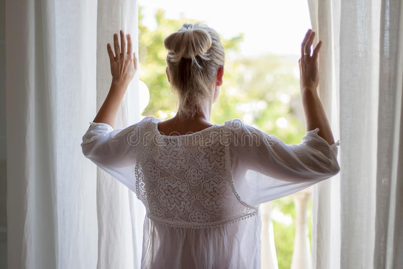 Kvinna som ut ser fönstret i pijama royaltyfria foton