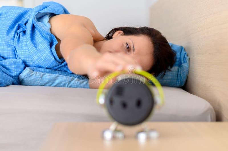 Kvinna som ut sträcker för att stänga av larmet arkivfoton