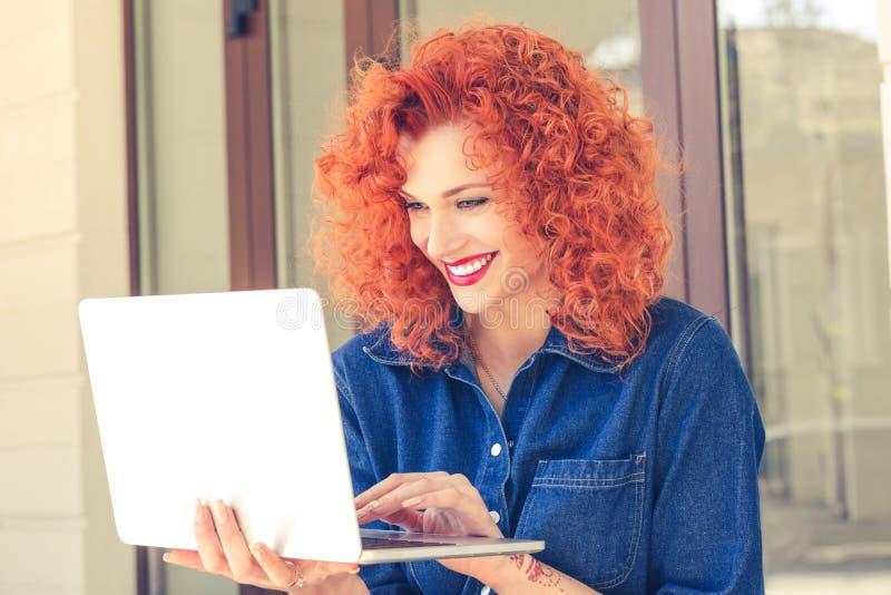 Kvinna som utanför sitter och arbetar på bärbara datorn royaltyfri foto