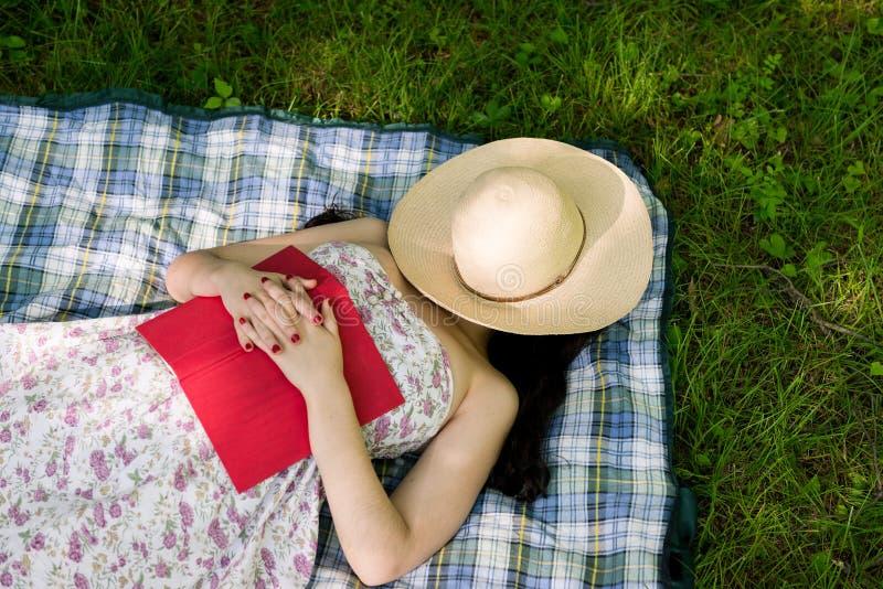 Kvinna som utanför sover i gräset royaltyfria bilder