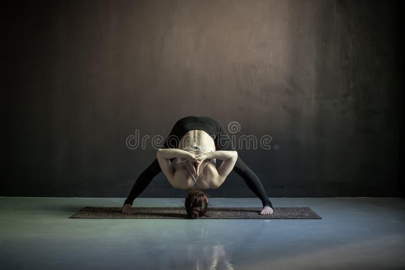 Kvinna som utarbetar göra den breda lade benen på ryggen framåt krökningen, Prasarita Padottanasana royaltyfria foton
