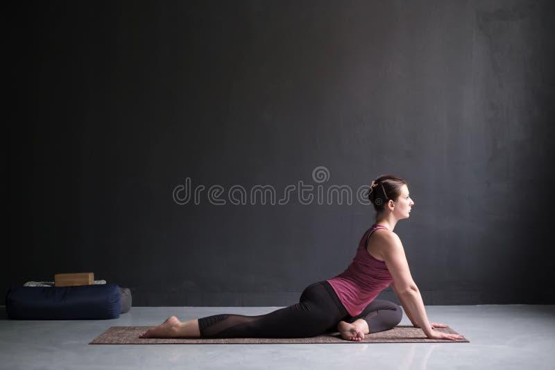 Kvinna som utarbetar göra lätt variation av en lagd benen på ryggen konung Pigeon Pose royaltyfri bild