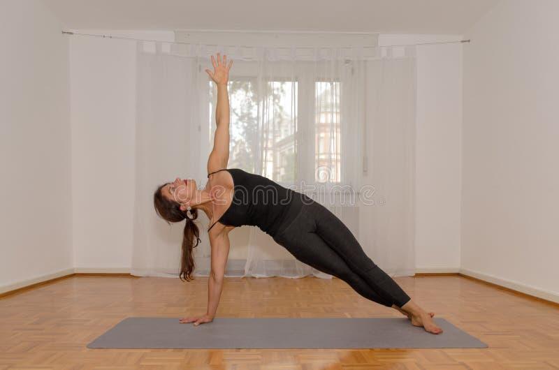 Kvinna som utarbetar göra yogaövningar royaltyfria foton