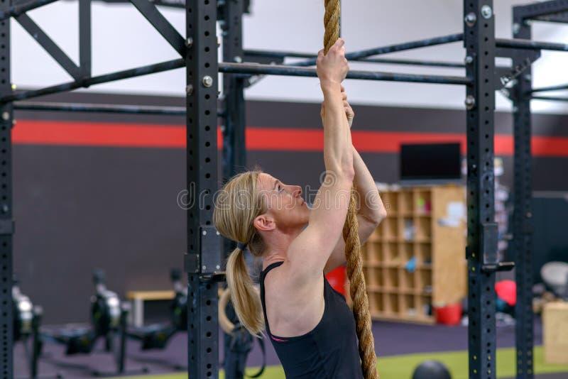 Kvinna som utarbetar på ett rep i en idrottshall arkivfoton
