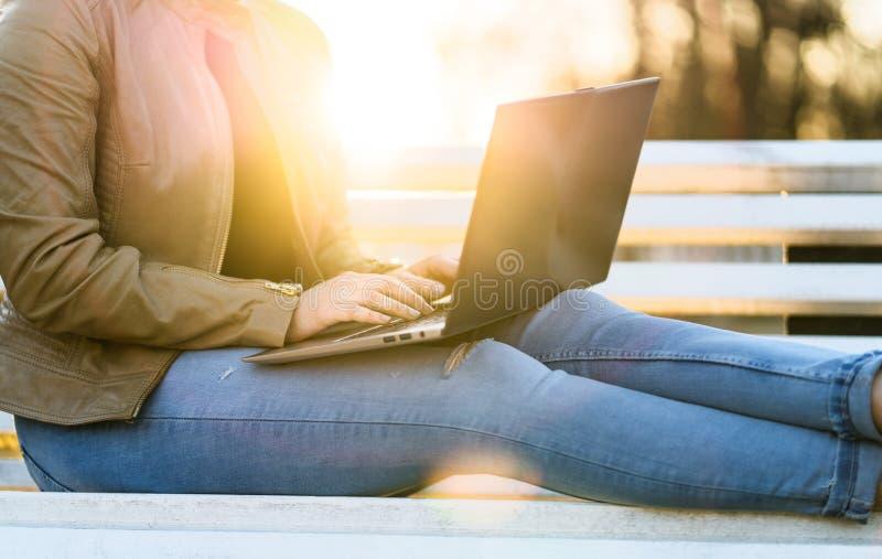 Kvinna som utomhus använder bärbara datorn i solnedgång royaltyfri fotografi