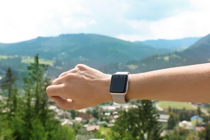 Kvinna som utomhus bär den smarta klockan med den tomma skärmen arkivfoto