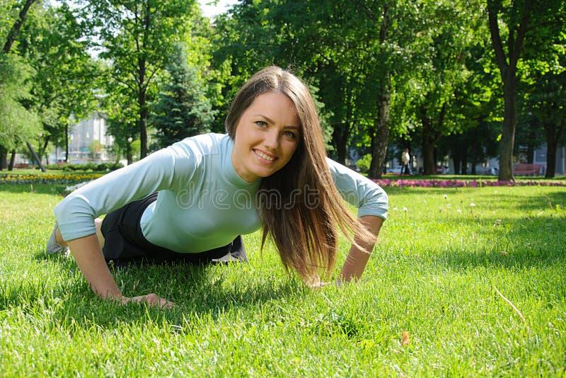 Kvinna som utomhus gör övning för bänkpress royaltyfria foton