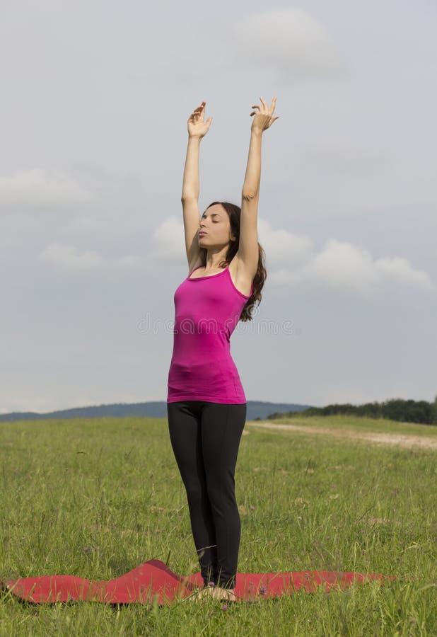 Kvinna som utomhus gör solhälsning i yoga fotografering för bildbyråer