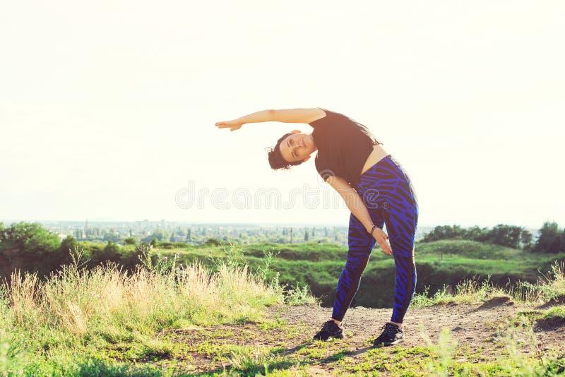 Kvinna som utomhus gör sportar på kullen fotografering för bildbyråer