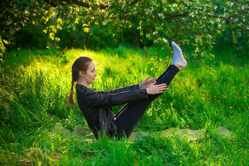 Kvinna som utomhus gör yoga på grönt gräs royaltyfria foton