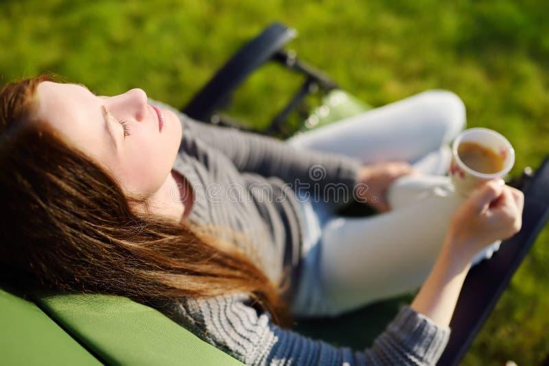 Kvinna som utomhus kopplar av med den stängda ögon och koppen kaffe i vardagsrumstol på en solig dag royaltyfri fotografi
