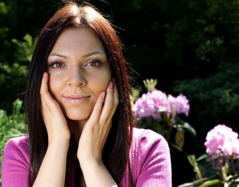 Kvinna som utomhus ler med några blommor arkivfoton