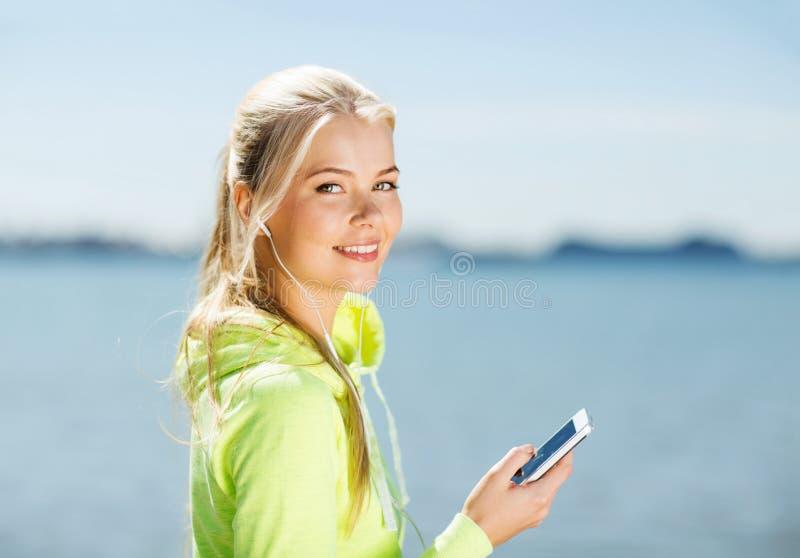 Kvinna som utomhus lyssnar till musik royaltyfria bilder