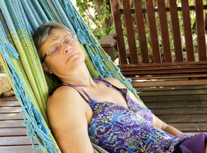 Kvinna som utomhus sover i en hängmatta royaltyfri foto