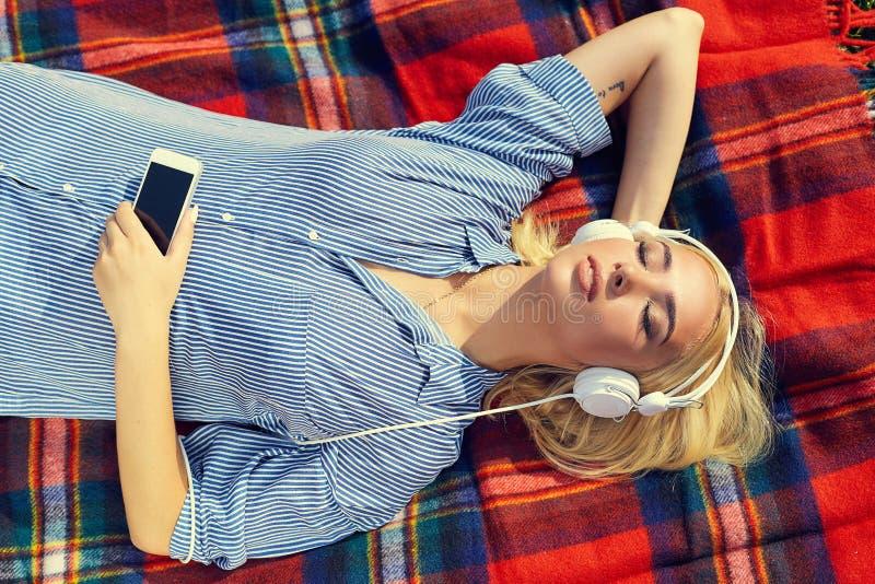 Kvinna som utomhus tycker om hörlurar för musik som ligger på gräs arkivfoto