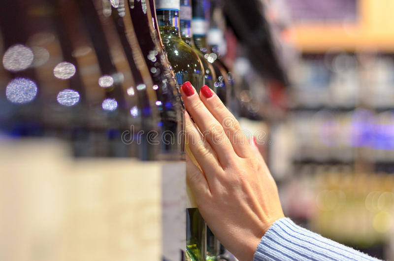 Kvinna som väljer av en flaska av vin - - hylla royaltyfri bild