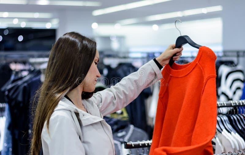 Kvinna som väljer den röda tröjan i lager begreppsshopping, försäljning royaltyfria foton