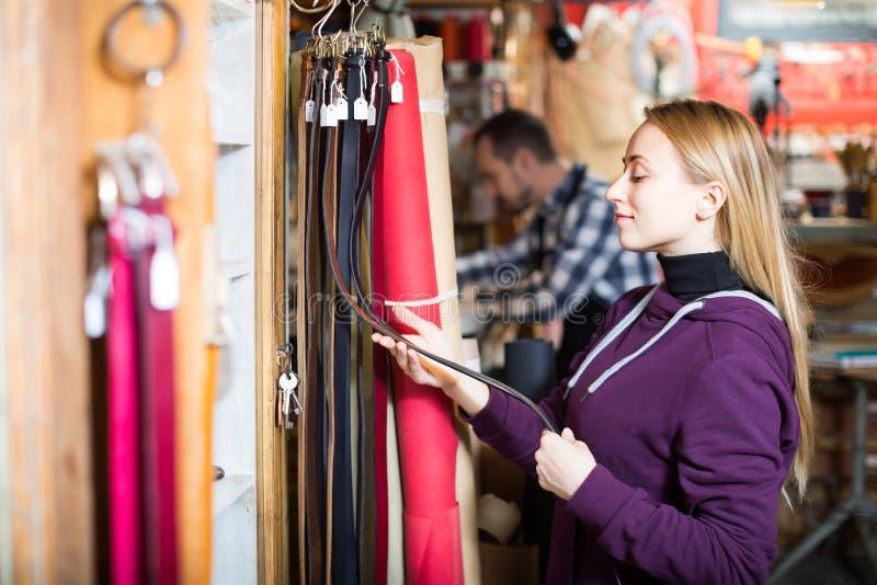 Kvinna som väljer det nya bältet i läderseminarium royaltyfria bilder