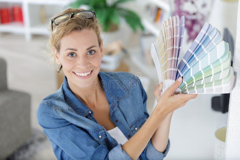 Kvinna som väljer färg för vägg från provkartor i rum fotografering för bildbyråer