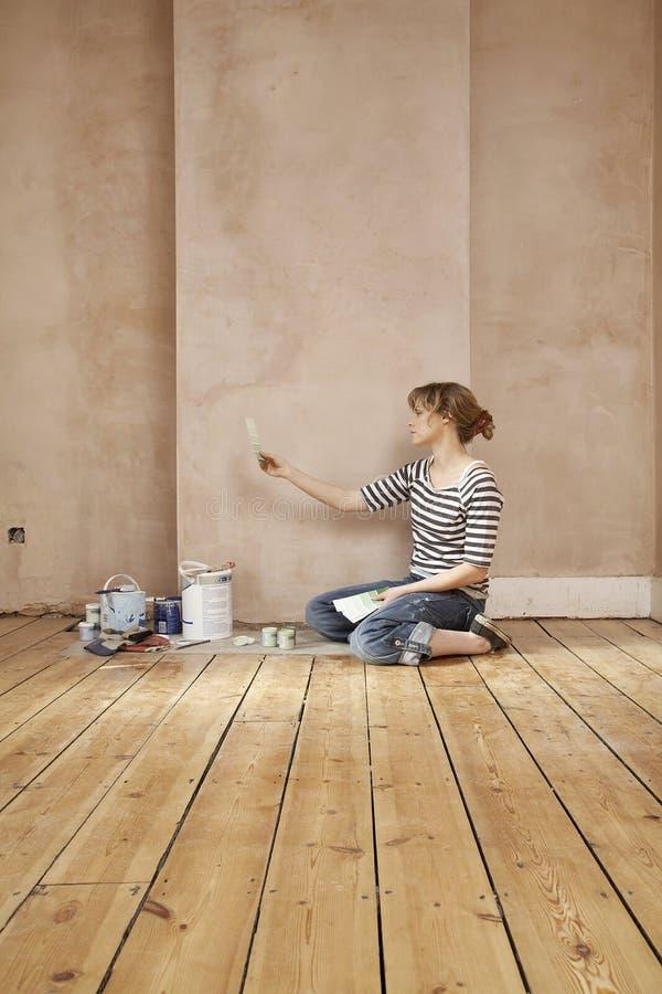 Kvinna som väljer färg från provkartor arkivfoton
