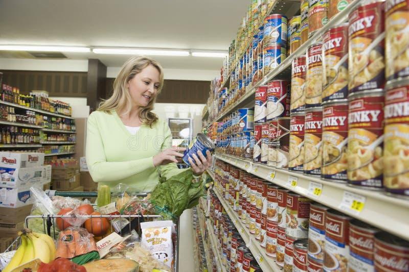 Kvinna som väljer förtennat gods i supermarket royaltyfri bild