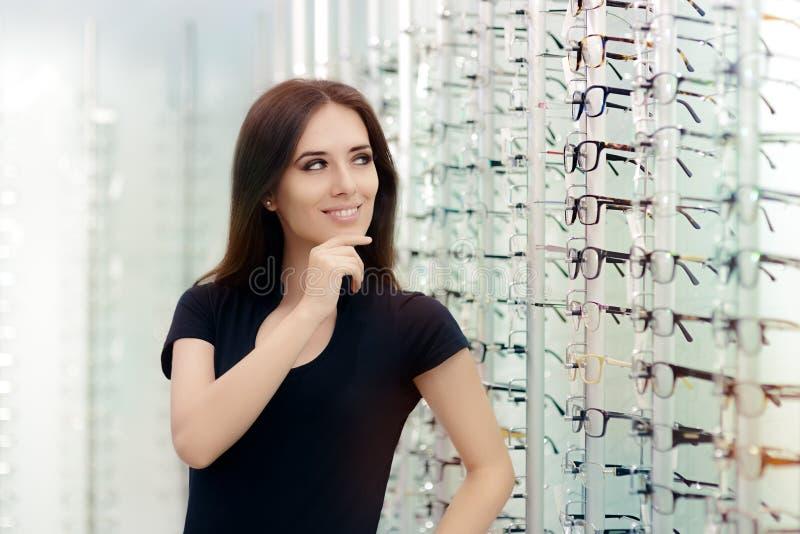 Kvinna som väljer glasögonramar i optiskt lager arkivbild