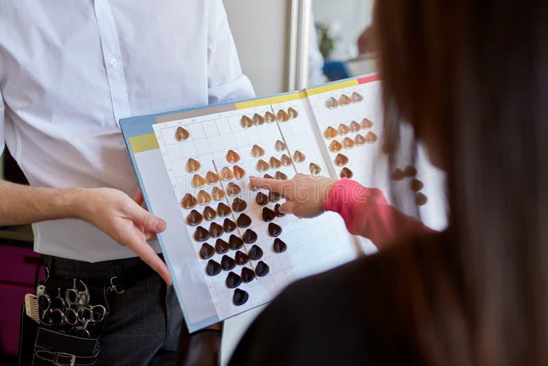 Kvinna som väljer hårfärg från paletten på salongen royaltyfria bilder